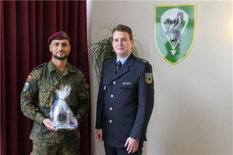 Gefreiter Taskin (links) mit Polizeioberrat Dennis Meyer  in der Kaserne Seedorf bei der Übergabe eines Geschenks für die gezeigte Zivilcourage.